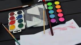 Le spazzole e le pitture dei colori luminosi con carta sono sulla tavola fotografie stock libere da diritti
