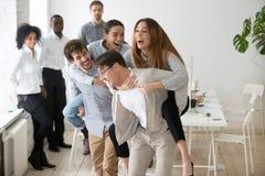 Le spelar kollegor som skrattar spela på ryggen ritt, i offic arkivbilder