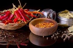 Le spezie e le erbe, la foglia di alloro, il pepe nero e la ciotola di legno di peperoncino rosso si sfalda Immagini Stock