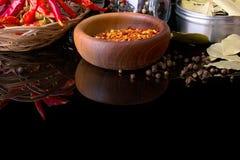 Le spezie e le erbe, la foglia di alloro, il pepe nero e la ciotola di legno di peperoncino rosso si sfalda Fotografie Stock