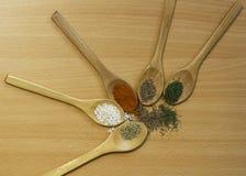 Le spezie sui cucchiai di legno pepano, riso, origano Fotografie Stock Libere da Diritti