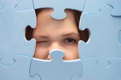 Le spie della ragazza con un puzzle blu Fotografie Stock Libere da Diritti