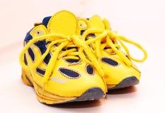 Le sport de bébé chausse des paires, couleur jaune Images libres de droits