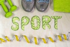 Le sport de mot est garni des concombres, contre le contexte des espadrilles, des haltères Photo stock
