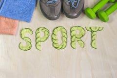 Le sport de mot est garni des concombres, contre le contexte des espadrilles, des haltères Image stock