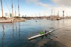 Le sport jumeau emballant le bateau à rames entre dans le port de port de Barcelone Photo stock
