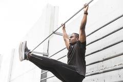 Le sportif concentré d'afro-américain réchauffant et étirant des jambes sur le pilier, tire vers le haut sur une barre horizontal images stock