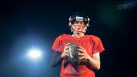 Le sportif dans l'uniforme rouge dispose à jeter une boule de rugby clips vidéos