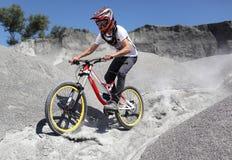 Le sportif dans les vêtements de sport sur un vélo de montagne monte sur les pierres photographie stock