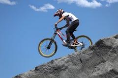 Le sportif dans les vêtements de sport sur un vélo de montagne monte sur les pierres photos libres de droits