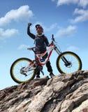 Le sportif dans les vêtements de sport sur un vélo de montagne monte sur les pierres photo stock