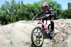 Le sportif dans les vêtements de sport sur un vélo de montagne monte sur les pierres images stock