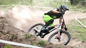 Le sportif dans les vêtements de sport sur un vélo de montagne monte sur les pierres photos stock