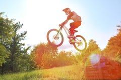 Le sportif sur un vélo de montagne vole dans un saut d'un tremplin photos libres de droits