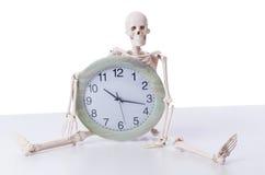 Le squelette avec l'horloge d'isolement sur le blanc Photographie stock libre de droits
