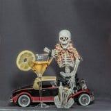 Le squelette se reposant sur la voiture classique tenant des clés de voiture et l'alcool boivent Photos libres de droits