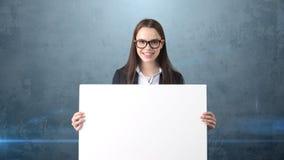 Le ståenden för affärskvinnan med det isolerade tomma vita brädet på grå färger Kvinnlig modell med långt hår i exponeringsglas Royaltyfri Fotografi