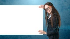Le ståenden för affärskvinnan med det tomma vita brädet på isolerade blått Kvinnlig modell med långt hår i exponeringsglas Royaltyfri Fotografi