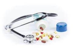 Le stéthoscope a drapé au-dessus d'une bouteille renversée de pilules image stock
