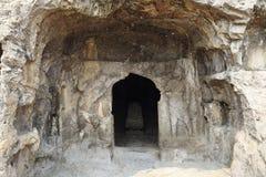 Le statue fini di Buddha delle grotte di longmen sono scolpite sulla scogliera nelle montagne Fotografia Stock