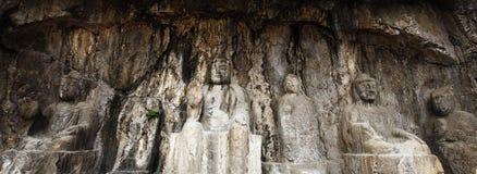Le statue fini di Buddha delle grotte di longmen sono scolpite sulla scogliera nelle montagne Fotografie Stock Libere da Diritti