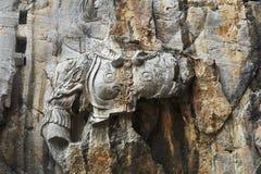 Le statue fini di Buddha delle grotte di longmen sono scolpite sulla scogliera nelle montagne Immagini Stock Libere da Diritti