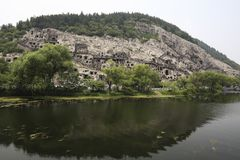 Le statue fini di Buddha delle grotte di longmen sono scolpite sulla scogliera nelle montagne Immagine Stock
