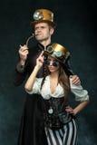Le steampunk de couples Un homme avec un tuyau et une fille avec des verres image stock