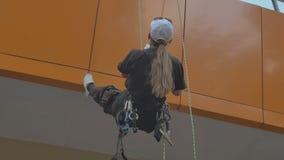 Le steeplejack de femme s'élève vers le bas sur l'équipement professionnel sur le bâtiment banque de vidéos