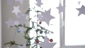 Le stelle di carta appendono su priorità alta di un abete di Natale accanto alla finestra Concetto di Natale Movimento lento 3840 archivi video