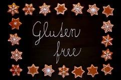 Le stelle ed i fiocchi di neve dei biscotti di natale del pan di zenzero con glassa bianca con il glutine del testo liberano su f Fotografia Stock