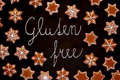 Le stelle ed i fiocchi di neve dei biscotti di natale del pan di zenzero con glassa bianca con il glutine del testo liberano su f Immagine Stock Libera da Diritti