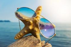 Le stelle marine in un simbolo di vetro di sole dell'oceano felice riposano immagine stock