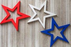 Le stelle rosse, bianche e blu di legno su un fondo rustico con la copia spaziano/quarte del concetto del fondo di luglio Fotografie Stock Libere da Diritti