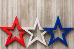 Le stelle rosse, bianche e blu di legno su un fondo rustico con la copia spaziano/quarte del concetto del fondo di luglio Fotografia Stock