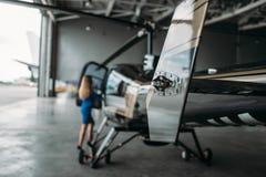 Le steward (hôtesse de l'air) féminin se tient contre l'hélicoptère photos stock
