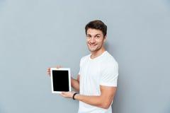 Le stiligt anseende för ung man och minnestavlan för tom skärm för innehav arkivfoton