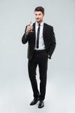 Le stiligt ungt affärsmananseende och hållande exponeringsglas av champagne royaltyfria foton