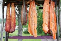 Le strisce canadesi del salmone rosso hanno appeso per fumare su uno scaffale all'aperto immagine stock libera da diritti