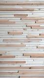 Le strisce di legno in due colori incollato alla parete Immagine Stock