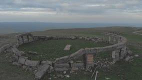 Le strutture del dopo-rilascio hanno sorvolato il livello antico rovinato dell'anfiteatro nelle montagne Sorvoli l'orbita 4K 100m stock footage