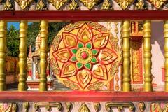 Le stuc d'or de la roue du dharma montre le symbole du bouddhisme quel décor dans le mur de Wat Pilok Temple Photo libre de droits