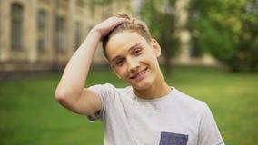 Le studenten som korrigerar frisyren mot universitet, studentutbyte arkivfoton