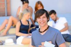 Le studentpojken med vänner utanför högskolan arkivbilder