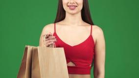 Le studio cultivé a tiré d'une femme souriant tenant des paniers montrant des pouces  banque de vidéos