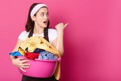 Le studio tiré de la femme au foyer de jeune femme avec le bassin rose, prêt pour des choses de lavage, porte la bande de cheveux image libre de droits