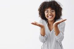 Le studio a tiré de la femme belle expliquant quelque chose les paumes de gesticulation et augmentantes simples dans naïf et inco photos libres de droits