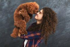 Le studio a tiré de la femme heureuse avec le chien bouclé mignon Photos stock