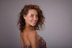 Le studio a tiré de la femme de sourire avec les cheveux bouclés bruns sains au-dessus du fond gris Image libre de droits