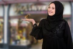 Le studio a tiré de la jeune femme portant l'habillement arabe traditionnel elle ` s jugeant le symbole de livre disponible photographie stock